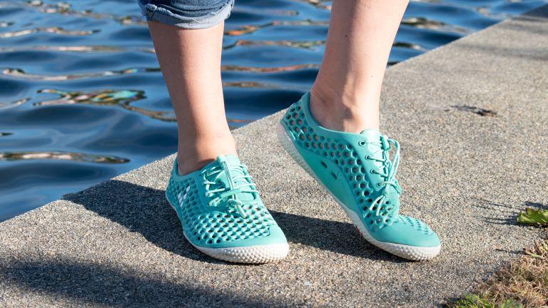 Person wearing Vivobarefoot Ultra Bloom III water shoes on waterside