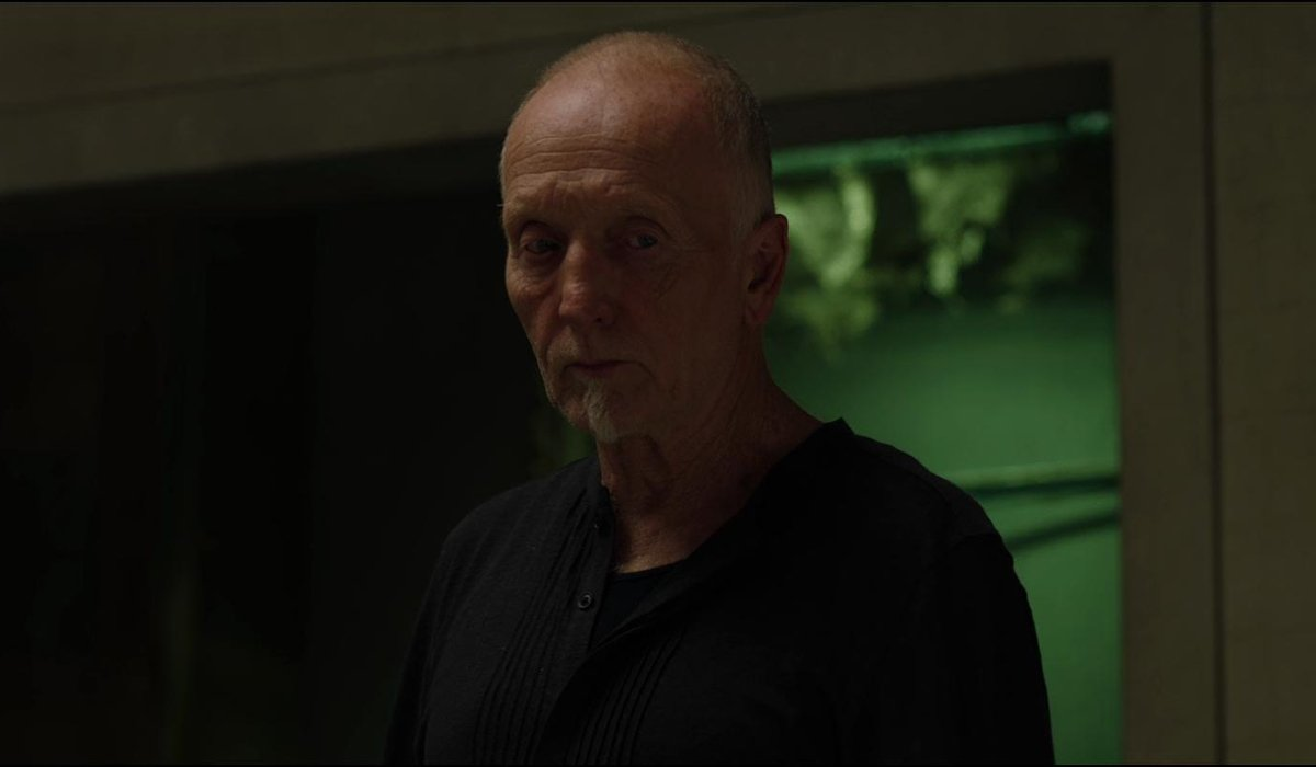 Tobin Bell stands very much alive in a room in Jigsaw.