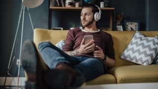 Man listens to music on his phone sat on a couch