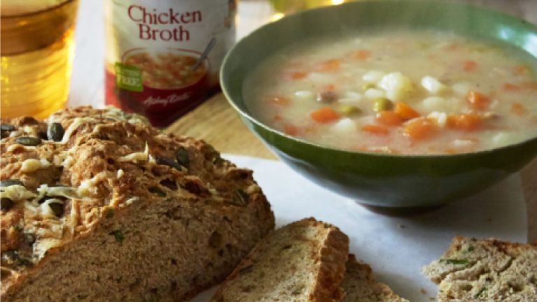 Cheese and chive Irish soda bread with bowl of steaming soup