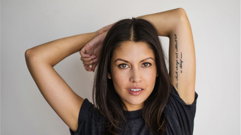 Woman with tattoo arms over head portrait - stock photo