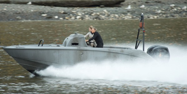 A Daniel Craig stunt double on a speedboat on the river Thames