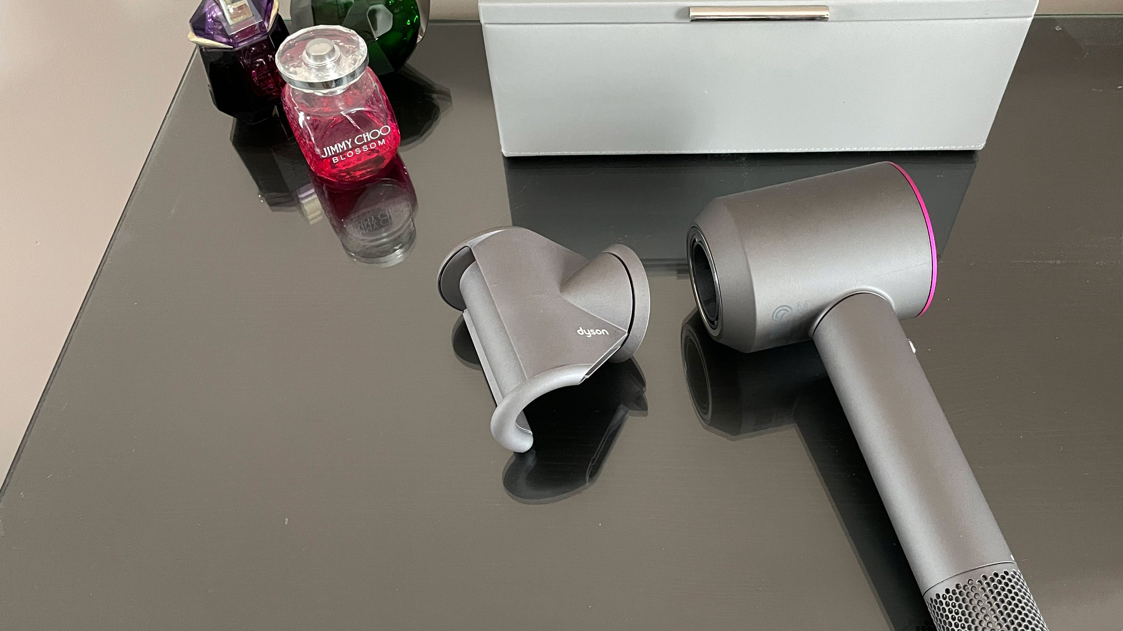 Dyson Supersonic hair dryer with fly away attachment next to it, on a dressing table