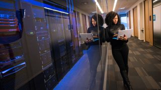 Woman stood working on laptop outside server room