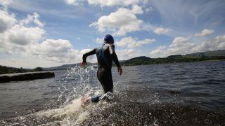 man running into a lake