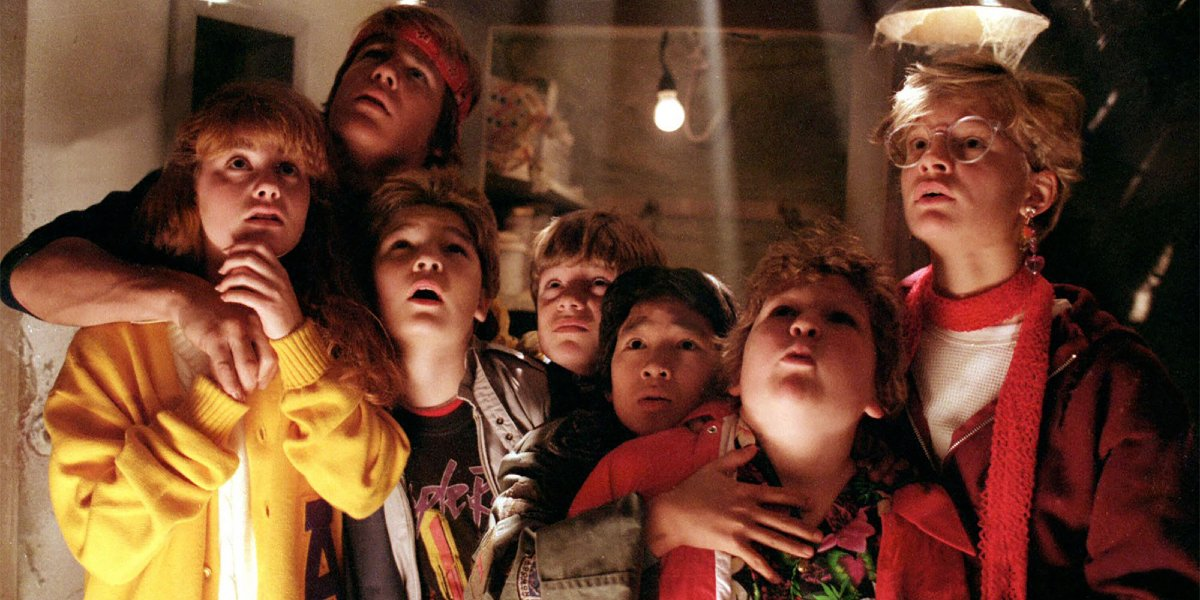 The Goonies cast looking up from their hiding place with concern