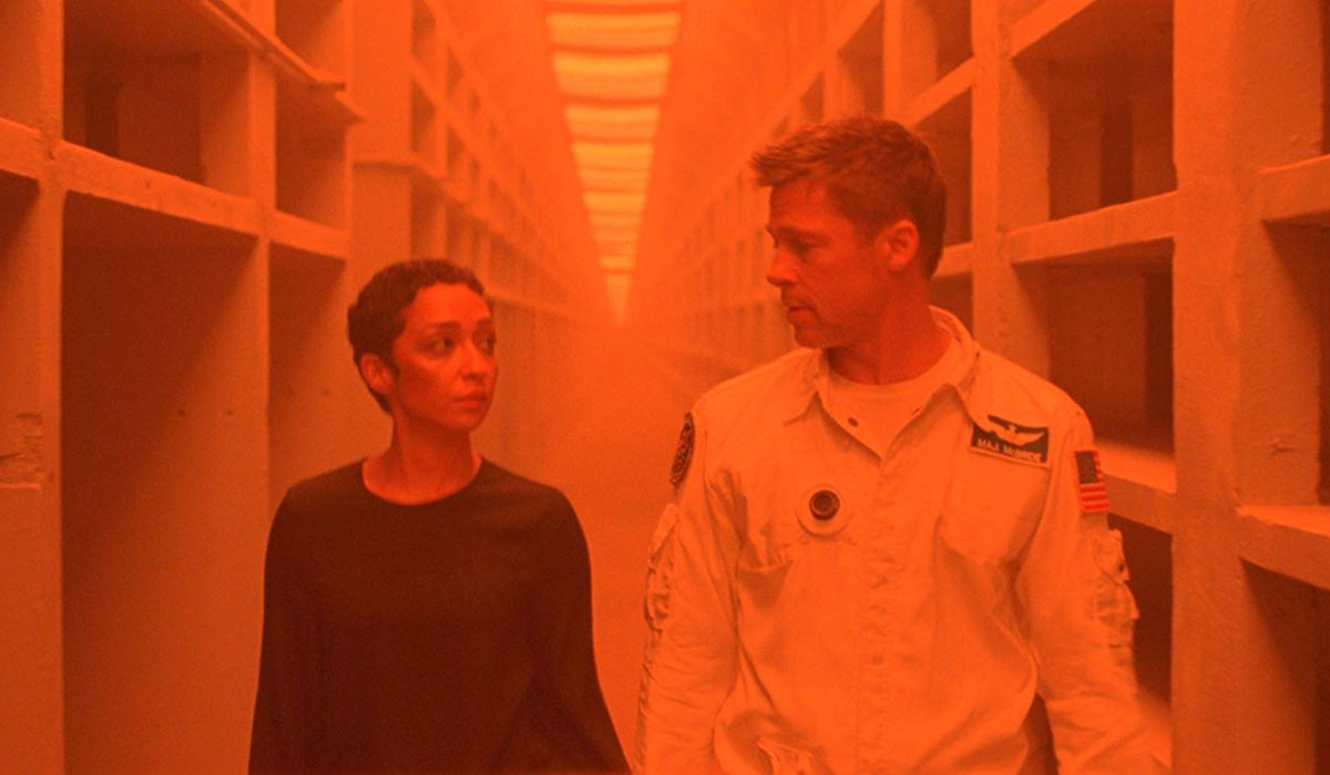 Ad Astra Ruth Negga and Brad Pitt walk through an orange lit hallway