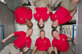 Inside the newly installed Permanent Multipurpose Module (PMM) on the International Space Station are the six crew members of the STS-133 crew.
