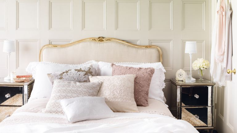 Pretty pink bedroom with upholstered cream and gold headboard