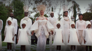 Beyoncé stands alongside a group of men, women and children dressed in all white in a scene from 'Black is King'
