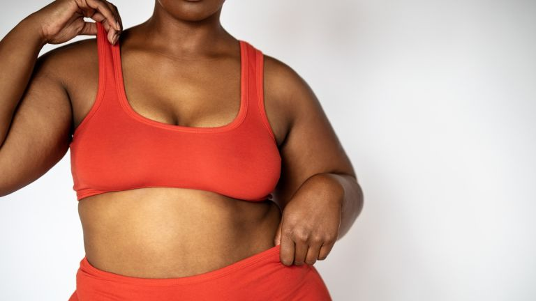 how bra sizing changes through your cycle: woman wearing a red crop top