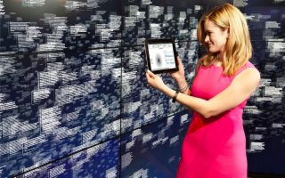 Woman stands holding a tablet next to a wall with words
