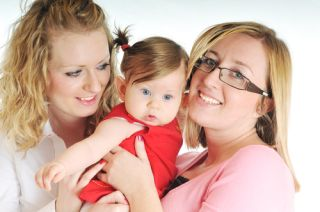 Two women hold a baby between them