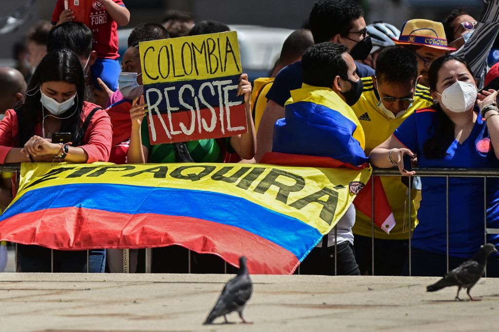 A woman with a group of Colombian fans holds a placard reading Colombia resists at the arrival spot on Piazza Duomo of the 21st and last stage of the Giro dItalia 2021 cycling race a 303km individual time trial between Senago and Milan on May 30 2021 Photo by MIGUEL MEDINA AFP Photo by MIGUEL MEDINAAFP via Getty Images