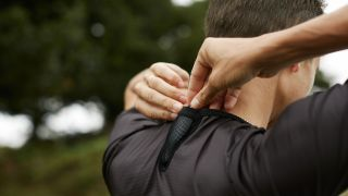 Man fitting Incus Nova device into the back of his running shirt