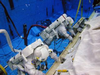 Astronauts Barbara R. Morgan (red stripes) and Janice E. Voss (solid white suit), wearing training versions of the Extravehicular Mobility Unit spacesuit, participate in an underwater simulation of extravehicular activity (EVA) at the Neutral Buoyancy Lab