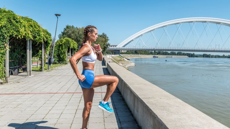 Young woman doing a HIIT workout outdoors in the city