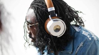 A picture of a man wearing Meters OV-1 headphones