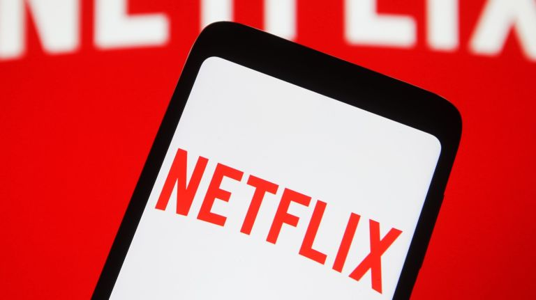In this photo illustration the Netflix logo seen displayed on a mobile phone and on a pc screen.