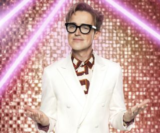 Tom Fletcher sports a white suit over a patterned shirt as he stands in front of a golden glittery backdrop