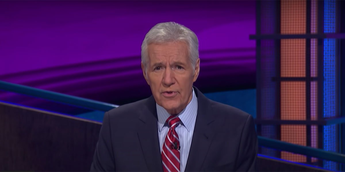 Alex Trebek addressing the audience while hosting Jeopardy.
