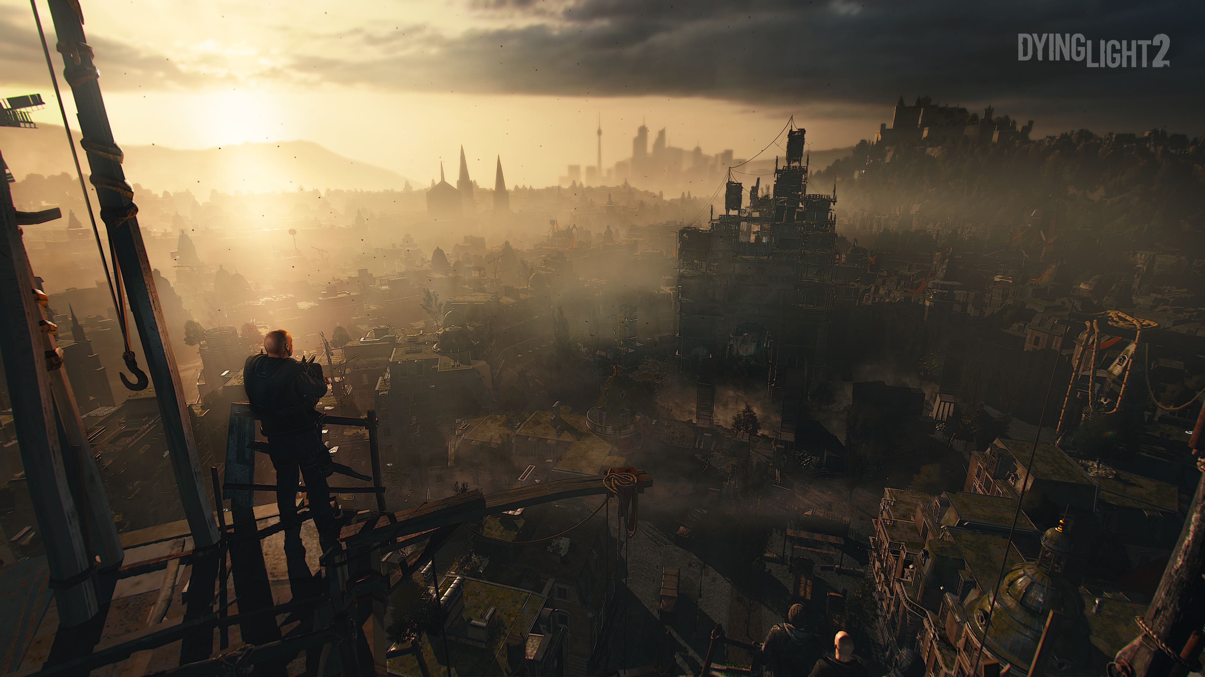 Dying Light 2 - A view from the rooftops down on sunset in the city.