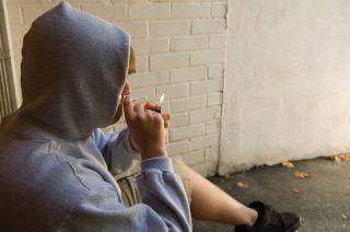A young man smokes a drug.