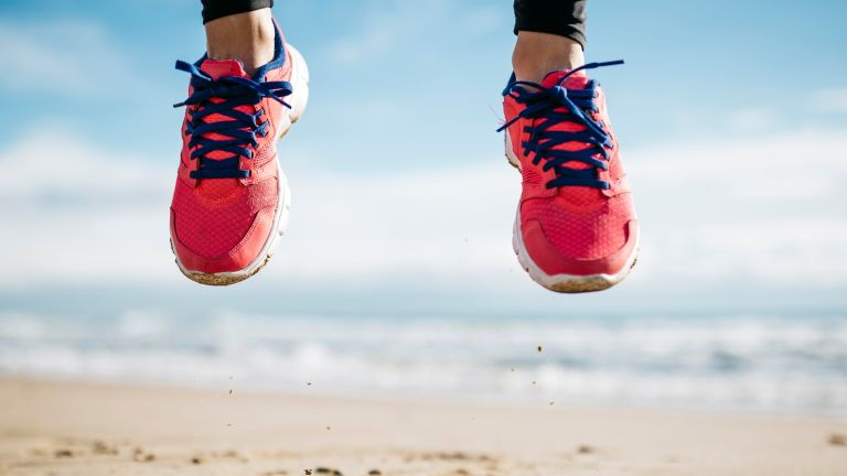 Best running shoes for women: Woman trainers beach jumping sand and sea