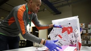 Election worker Erick Moss sorts vote-by-mail ballots for the presidential primary at King County Elections in Renton, Washington, on March 10, 2020.