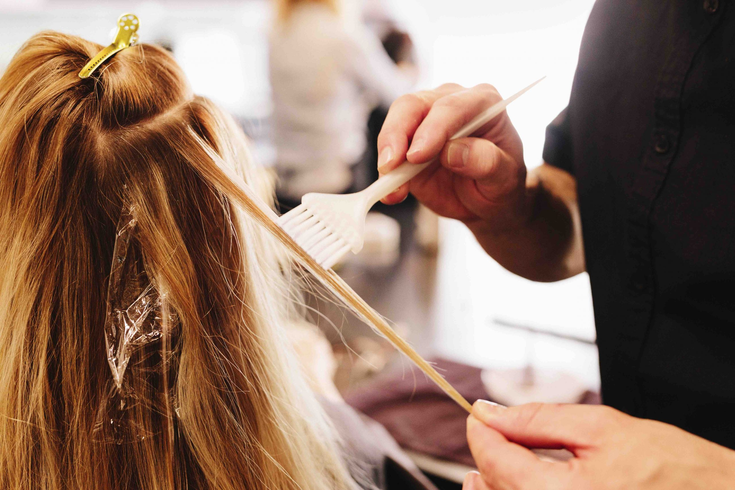 hairdresser putting hair dye on woman's head