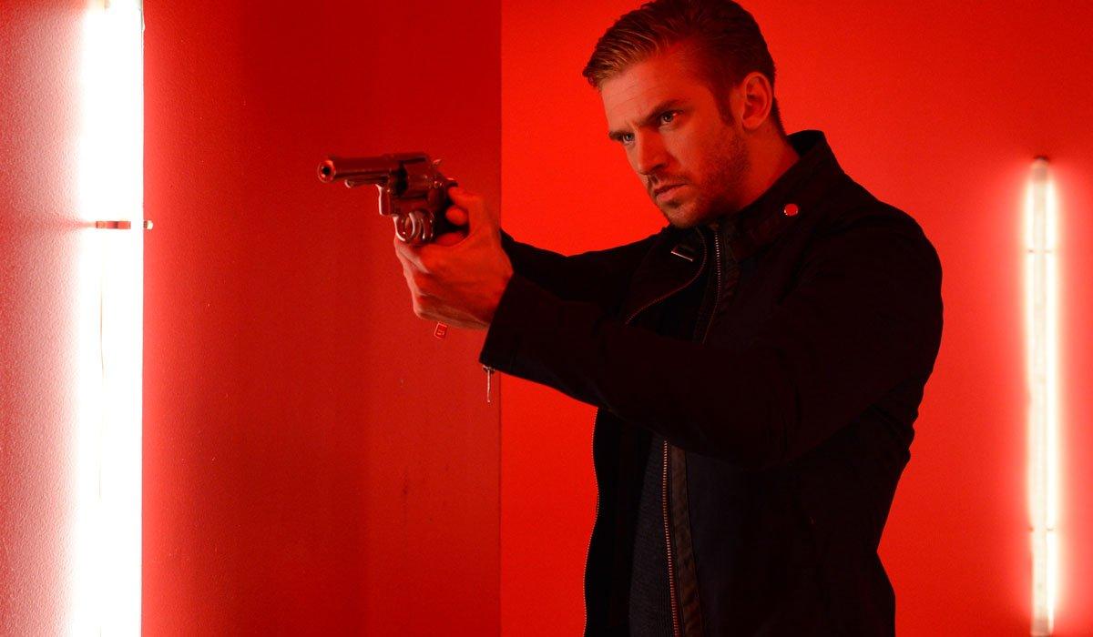 Dan Stevens aims his gun in a fun house in The Guest