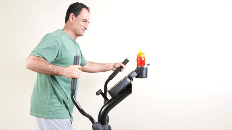How to use an elliptical machine: middle-aged man working out on a cross-trainer