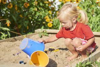 A little girl plays in a sandbox.