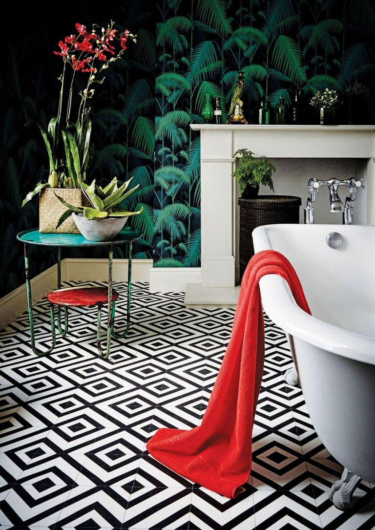bathroom with monochrome patterned flooring, pattern clashing wallpaper, a freestanding bath and small side table with house plants