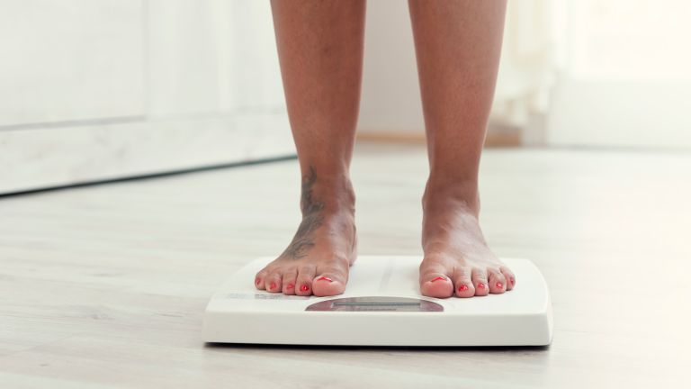 Women weighing herself on scales