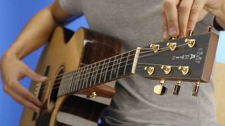 Man tuning acoustic guitar
