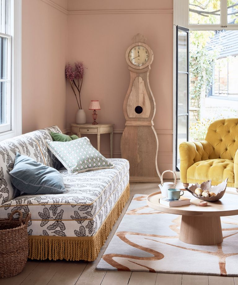 Bohemian living room ideas featuring a patterned, fringed sofa with rug, coffee table, Swedish clock and yellow armchair