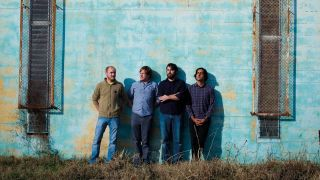 Explosions In The Sky leaning against a blue wall