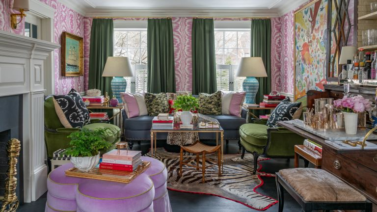 A living room with pink and white wallpaper, green curtains, artwork and an eclectic mix of multicolored wallpaper in a maximalist style