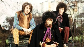 A photograph of Jimi Hendrix sat outside on a park bench