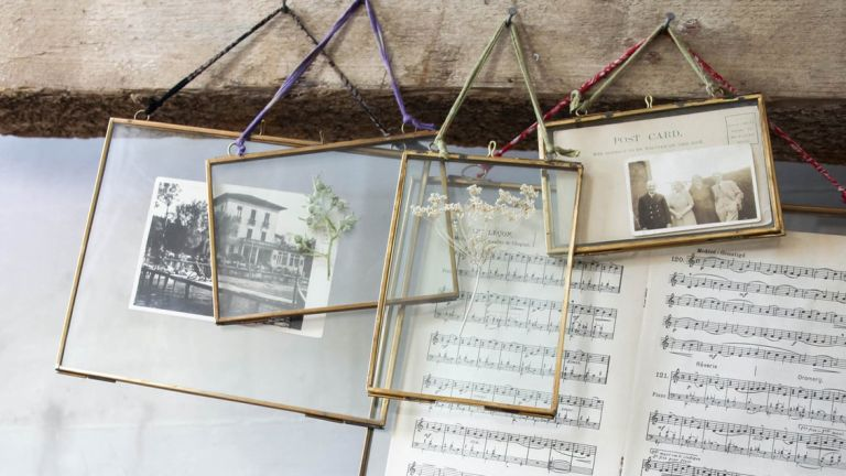 gold picture frames with a post card and music notes