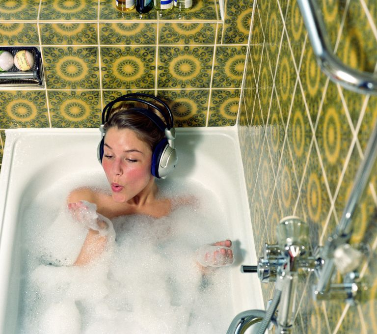 Young woman wearing headphones in bath blowing foam from hand, self-care day ideas