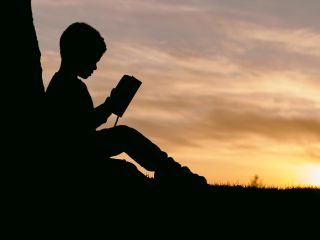 Silhouette of boy reading traditional book