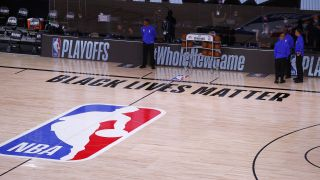 Referees stand on an empty court after the Milwaukee Bucks refused to play Wednesday in Orlando.