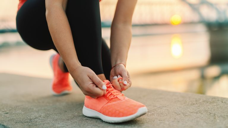 good running shoes: woman lacing up trainers