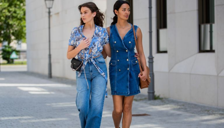 Giannina Haupt and Alyssa Cordes is seen wearing 70s fashion trends like denim jeans, denim dress, top with floral print, black bag, brown bag, white sneakers and sandals, total look Liu Jo on June 14, 2021 in Berlin, Germany.