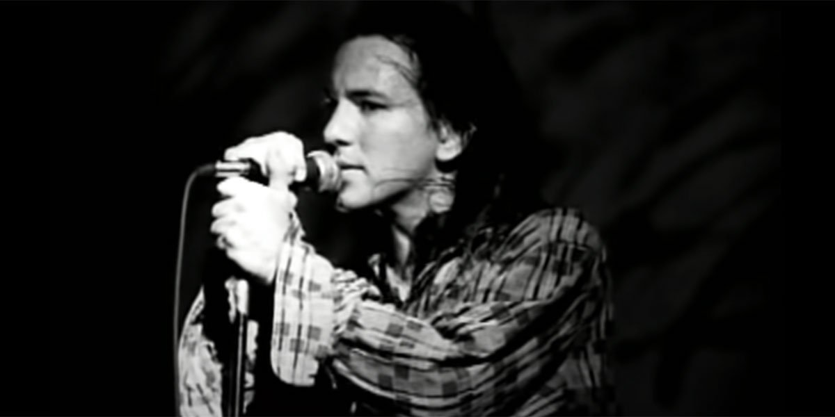 Eddie Vedder with a plaid shirt on singing into a microphone in black and white.