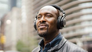 a smiling man wearing the audio-technica ath-m50xbt2 headphones