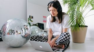 Download Adobe Audition: Woman using laptop and wearing headphones