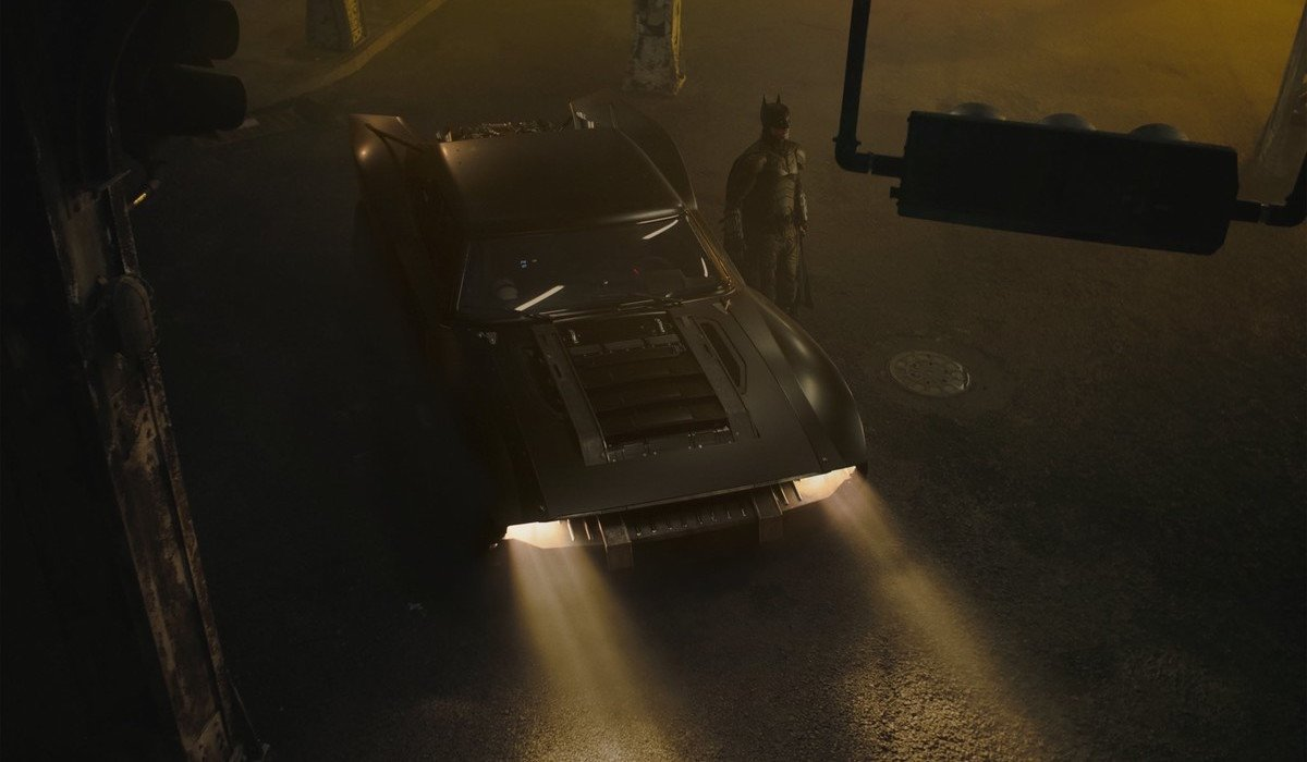 Robert Pattinson's Batman next to Batmobile